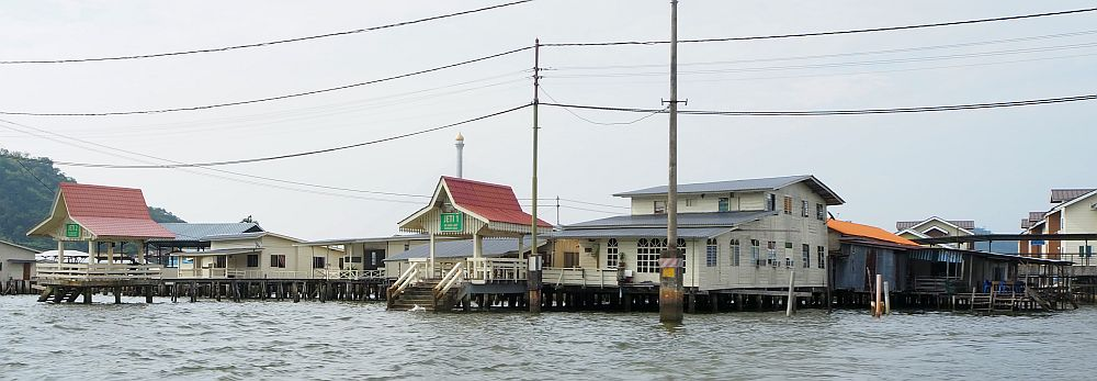 White houses on stilts over the water, and two small roofed quays extend out from them. Electric lines cross the top of the picture on poles in the water.