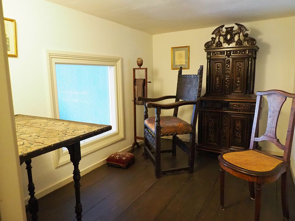 A low-ceilinged room, quite plain. The window is low near the floor on the left. Plain wood flor with two simple wooden chairs, a small carved secretary and a table.