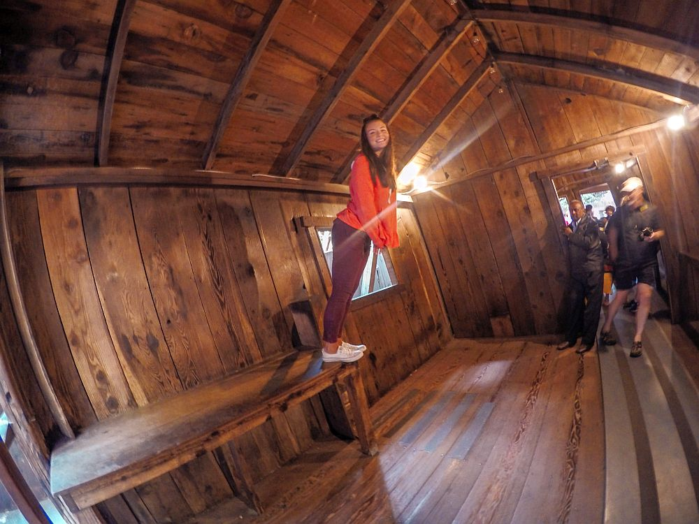 Inside a building in the Mystery Spot: the walls, floor and ceiling are all wood, but the people all seem to lean to the right, as if gravity isn't pulling them down but slightly to the left.