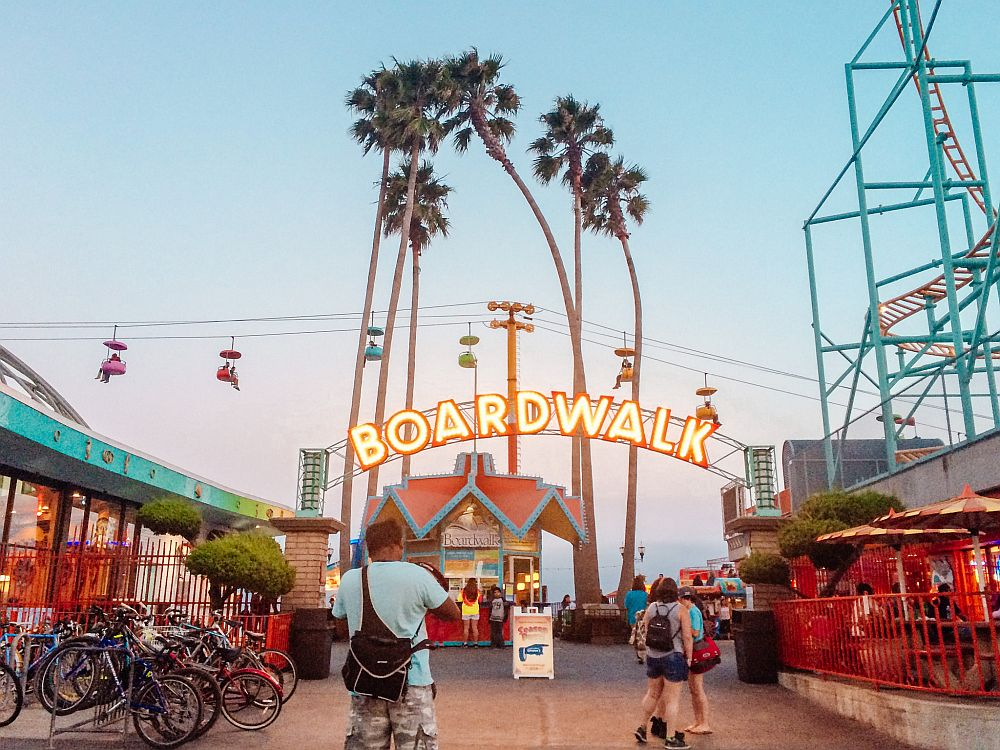 """Looking down the boardwalk: a small kiosk straight ahead with an arched neon sign above it that reads """"boardwalk"""". TO the right a small part of a roller coaster track is visible. Behind the kiosk in the center is a group of about 6 very tall narrow palm trees. Beyond that is a horizontal cable where seats dangle along its length."""