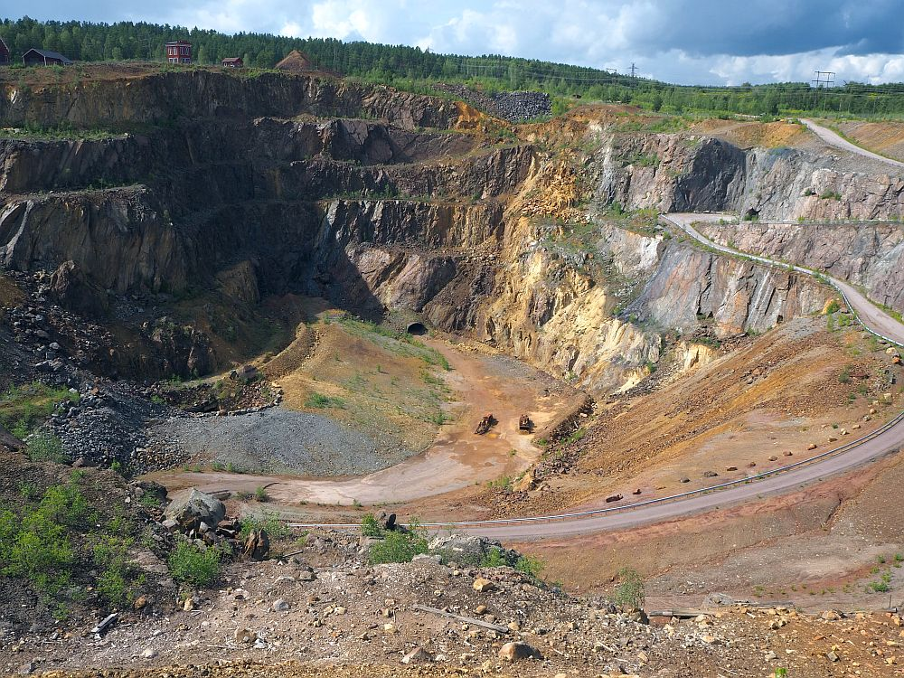 A deep pit at Falun Copper Mine, showing bare rock around the sides, some of which is reddish. A dirt road snakes down to the bottom and two tractors are visible, very tiny, at the bottom.
