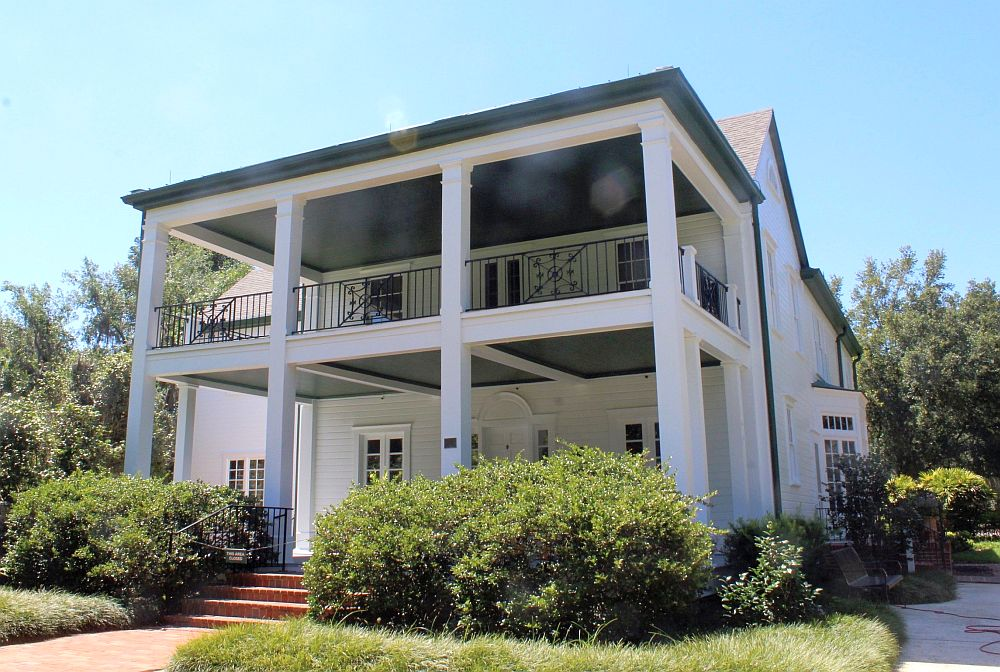 The house is two stories tall and white. In front is a two story veranda held up on some simple square pillars. The upper verandah has an iron railing around it. Shrubs partially hide the lower verandah.