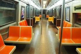 Looking down the length of a subway car. Harsh light from above, seats along the sides or perpendicular to the sides (in sets of 2). The seats are bright orange molded plastic.