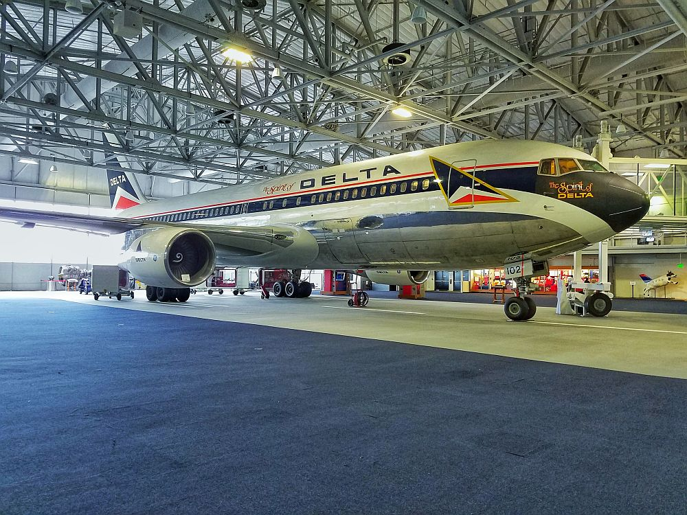 A large airplane inside a cavernous warehouse of a room (steel beams holding up a metal ceiling). The plane (a 737?) has the Delta logo and paintwork.
