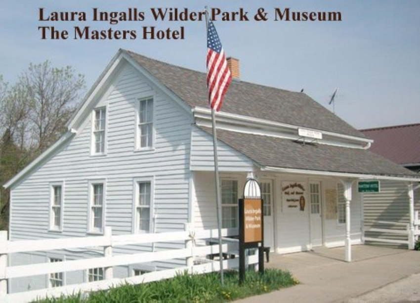 A white building with a gray roof and a roof over the sidewalk in front, supported on 3 slender pillars. The house has 2 stories, with another story partially visible down below street level on the side, where the ground slopes down. A flag on a flagpole in front of the building. Text above it: Laura Ingalls Wilder Park & Museum The Masters Hotel.