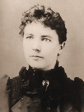 a black-and-white photo of Laura Ingalls Wilder: hair pulled back, short-cut bangs, eyes looking off to the left a bit, Black high collar.