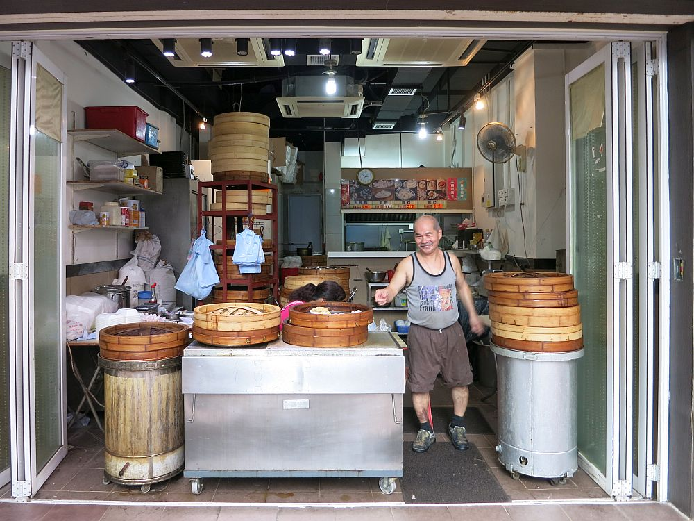 The entire storefront is open to the street with glass doors folded back to the sides. A table in the middle holds baskets used for steaming dim sum. A man, smiling in a sleeveless shirt and shorts, stands between the table and a cylindrical table of some sort with another pile of the baskets. Behind is the whole kitchen, with various supplies visible and a fan fixed to the wall.