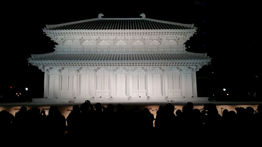 It is nighttime, but the snow sculpture at the center of the photo is well-lit. It is a detailed model of a building, perhaps a traditional temple with vertical columns and a tiled roof that curves up slightly at the outer edges. It seems similar to traditional palaces or temples in South Korea.
