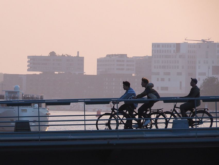 Three young men bicycle across a bridge in Amsterdam, sillhouetted against a darkening sky with tall buildings in the background.