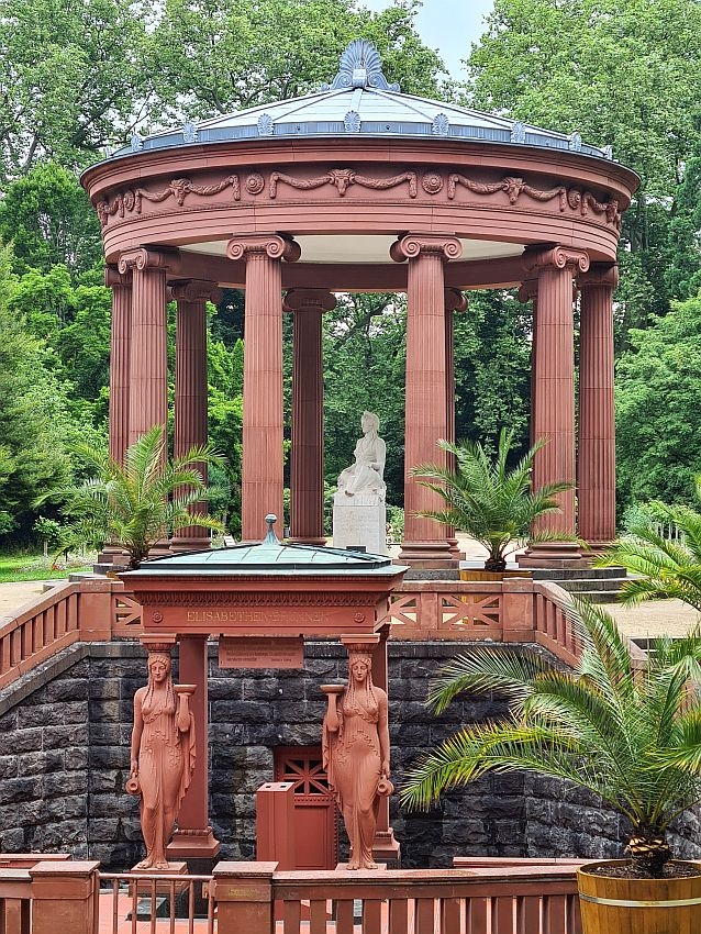 In front, a small room is held up on two classical pedestals and on the heads of two statues of women, all in dark red stone. Stairs rise on either side of this spring and above and behind the spring is a larger structure: a circle of ionic columns in the same dark red stone holds up a round roof of metal - perhaps copper. This structure shelters a statue of a woman in white stone.