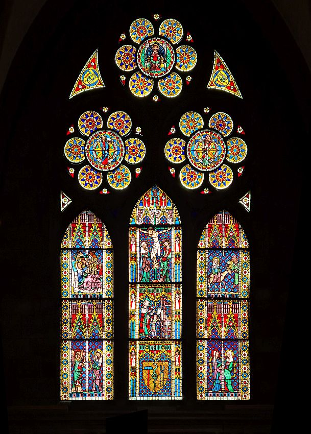 A vertical stained glass window with many many panels. At the top, 3 circular panels, below: 3 vertical panels with arched tops. The pictures visible in the glass show events in Jesus's life: the crucifixion is in the center top of the middle vertical panel. The bottom of the center panel has a cress with a sledgehammer and tongs on either side of a snake.
