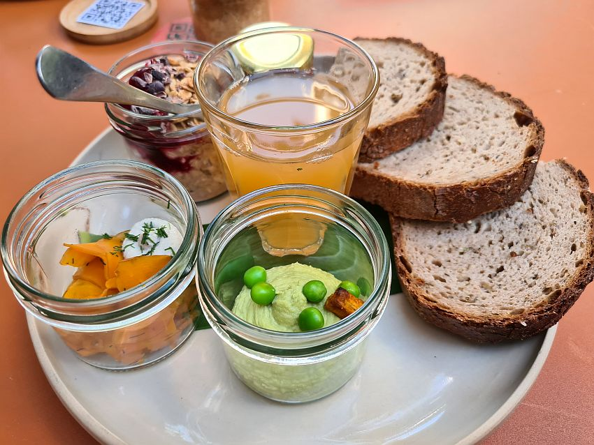 Three slices of round brown bread on the right, arranged to overlap. In the front, pea mush with a few whole peas on top in a small jar without a top. Left of that, a salad of some sort, mostly carrot, also in a small pot. Beyond that on the left, oatmeal with some berries on top and a spoon sticking out, also in a small pot without a lid. A glass of apple juice in the center. A jar of jam is behind, but only the lid is visible.