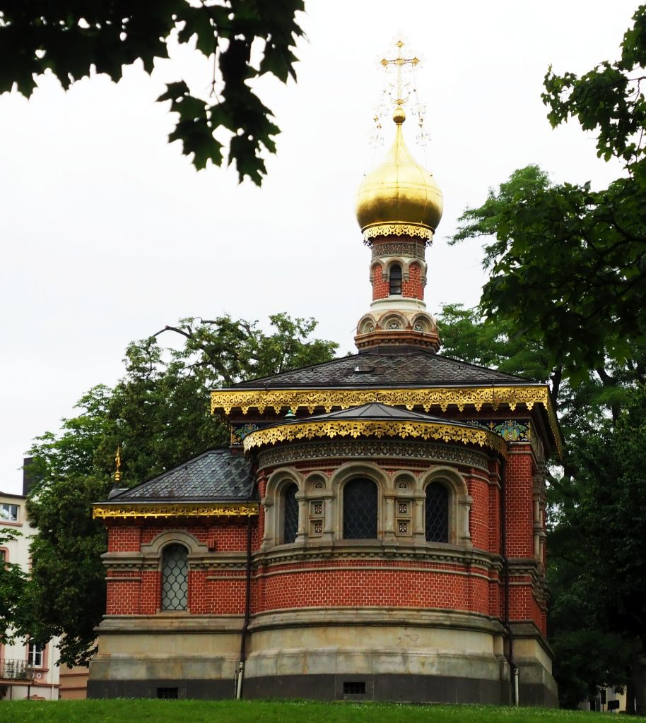 The church is made of red brick and has a rounded section in front that I assume is the altar. It's a very small building and the small steeple is round, with an onion dome on top. The dome is gold as is a filigreed edging around the roof lines below.