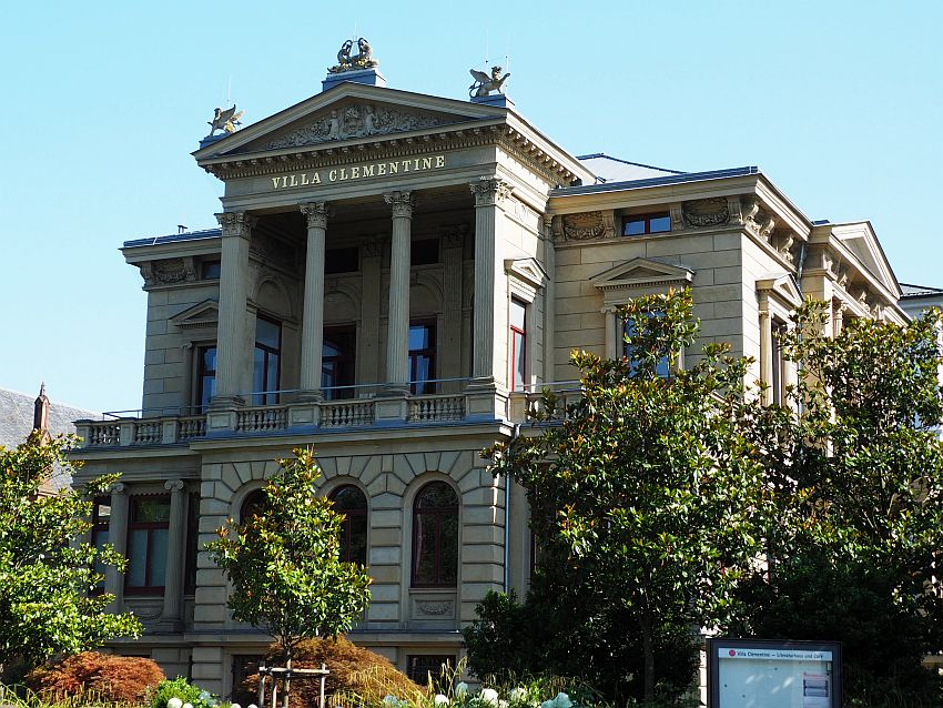 A brownish color stone siding. PIllars hoding up a pediment on the upper floor, with a bas-relief in the pediment and statues of winged lions above that on the corners of the pediment. The rest of the building is somewhat simpler.