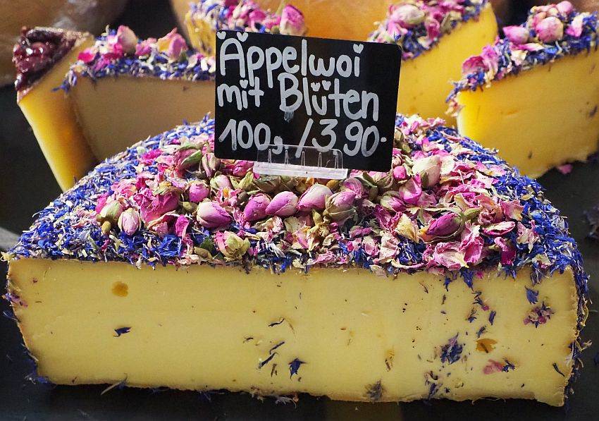 A half-round of cheese, cut so the cheese is visible, but the top is covered with what looks like rose buds and some other bluish-purple small flower. The sign on top of the cheese reads Appelwoi mit Bluten 100 g/3.90.