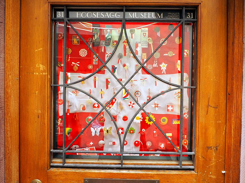 A window says Hoosesagg Museeum at the top and the number 31. A cloth covers the window behind its glass; the cloth shows the swiss flag: red with a big white cross in the middle. On the cloth are many small items: ribbons and flowers and such, almost all in red and white and many showing the same Swiss cross.