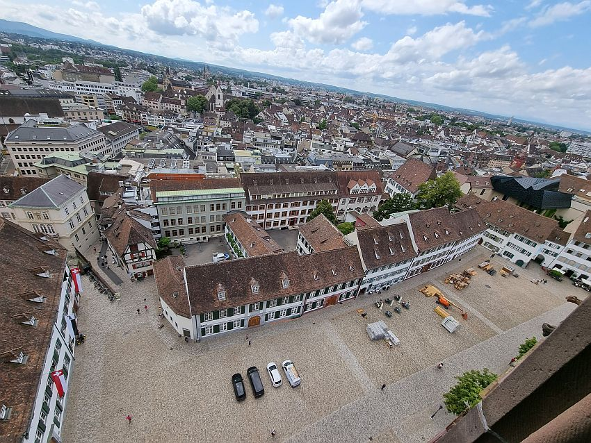 Looking down on Munsterplatz, the open square around the cathedral. It is lined with neat buildings of 3-4 stories. All are painted white and have neat rows of windows on each floor, with shutters open. Beyond the  Munsterplatz the view looks over the roofs of the city, all quite low on this side of the city.