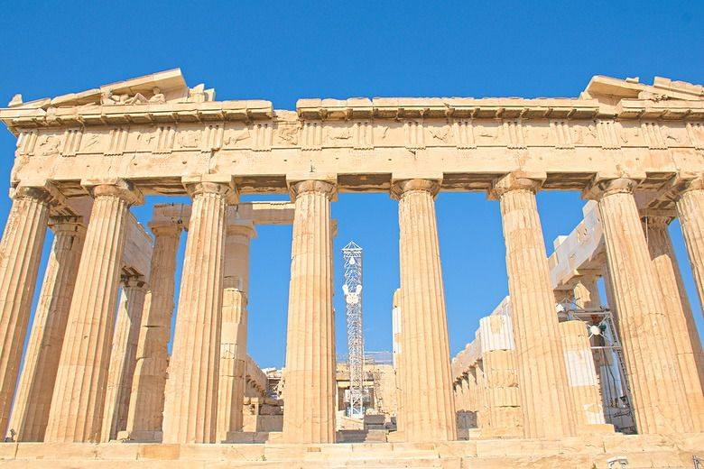 A front view of the parthenon, with a row of ionic columns across the front, each slightly larger at the bottom than the top. The columns hold up the bottom of the pediment,  but the top is gone, except for the very outer corners. Beyond the columns some of the side pillars are visible on either side, and a tall modern crane is visible right in the center.