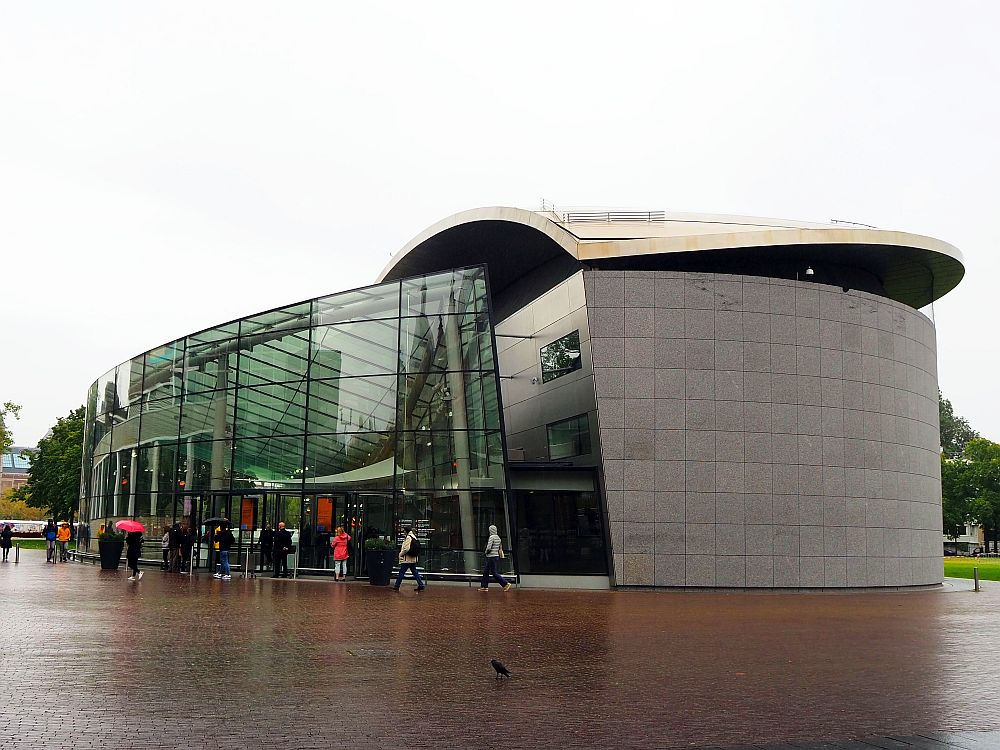 The Van Gogh Museum is a modern structure: On the left, a rounded wall several stories high made of glass. On the right, a grey-sided curved building with a curved white roof.
