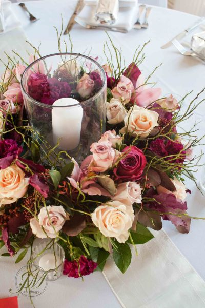 Burgundy and peach wedding table arrangements  A floral wreath with     Burgundy and peach wedding table arrangements  A floral wreath with  incorporated candle in a hurricane