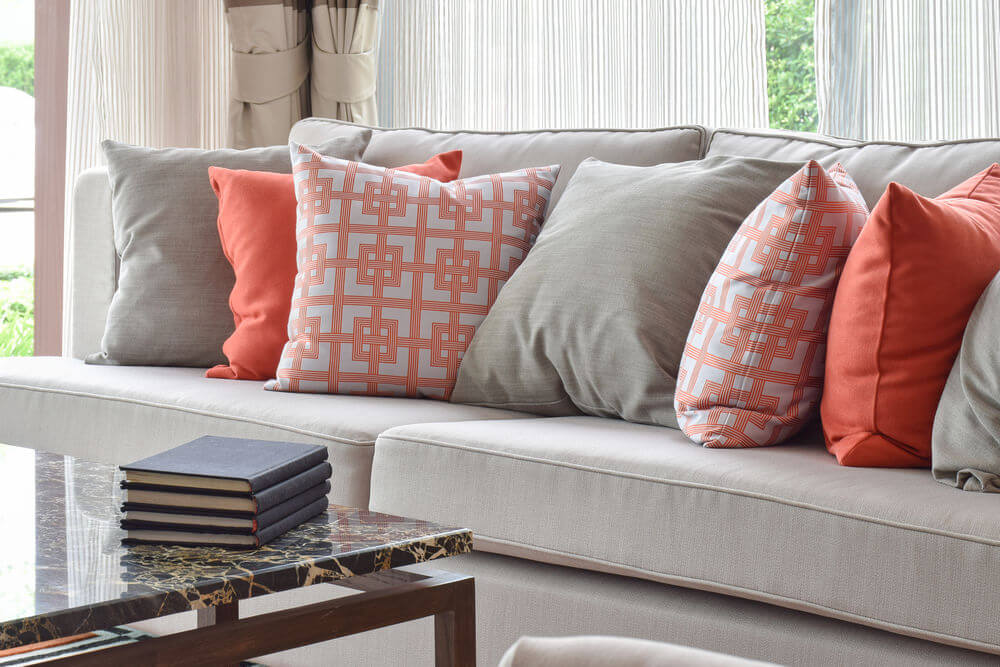 35 Sofa Throw Pillow Examples  Sofa D    cor Guide    Home Stratosphere Light grey sofa with a mix of bright orange and matching solid grey throw  pillows