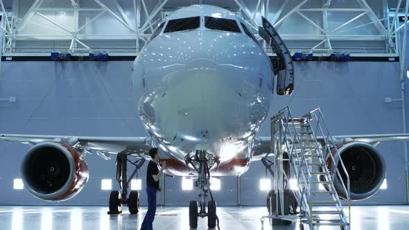 Aircraft Maintenance Engineer Inspects Plane With A