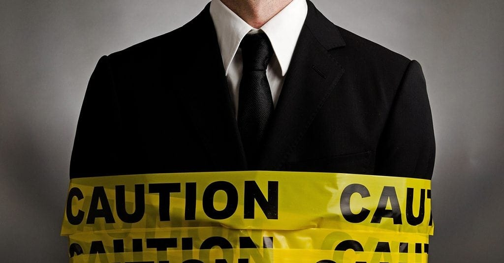 man in a black suit with caution tape wrapped around him.