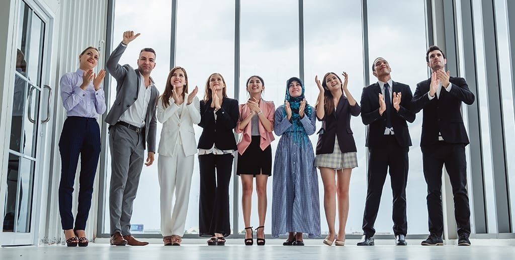 Group of diversity business people celebrating clapping hands for teamwork and successful