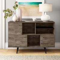 Minimalism and mid-century modern style come together in this 53'' W x 18'' D buffet table! Crafted from manufactured wood in a rustic woodgrain finish, this clean-lined design strikes a rectangular silhouette with four flared tapered round legs, which are also removable. Three side cabinets offer out-of-sight storage for table linens, while three open center shelves allow you to display everything from your favorite vases to extra plates. Plus, there's plenty of room up top for a lamp or other...