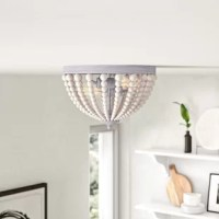 Bring boho style all the way up to your ceiling with this 2-light flush mount. Crafted from metal, its base, sockets, and finial are finished in a distinctive brushed gray finish. Inside, two 60W bulbs (not included) brighten up your hallway or entryway. Instead of a glass shade, this flush mount has strands of wooden metal beads that surround its bulbs for a laid-back effect. This fixture is compatible with sloped ceilings and dimmer switches.