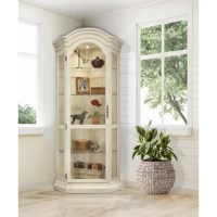 This charming corner curio cabinet has tons of character. Beaming with handcrafted pride, this curio cabinet features a light with five glass shelves and one glass door to proudly display and protect your most prized items. This versatile corner curio cabinet will solve all of your spatial needs by utilizing that unused space in the corner while putting your cherished items on display! Finished in a distressed sand shell white, this corner curio cabinet is constructed out of solid hardwoods and...