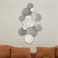 Visually rhythmic, this statement wall art decor is comprised of eye-catching white washed and gray roundels that feel rustic yet modern at the same time. Handcrafted of durable iron and painted,  the 11 connected rounds offer distinct character, size and texture.  Each piece is unique due to its artisanal nature and no two will be exactly alike.   Well sized, this piece measures as  follows: 2.75 L x 43.25 W x 23.5 H inches (7.0 L x 110.0 W x 60.0 H cm).          Luxurious and layered with...