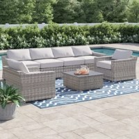 This 7-piece sectional set is crafted from handwoven wicker on rust-proof aluminum frames for an inviting outdoor seating group that'll take you from summer BBQs to chilly evenings with hot cider. It comes with an extra-long sectional sofa, two club chairs, and a paneled coffee table, all on top of nylon feet that won't scratch your patio floor. The thick foam-filled seat cushions have a sloped design for extra back support, plus removable covers for easy washing. It all comes fully assembled...