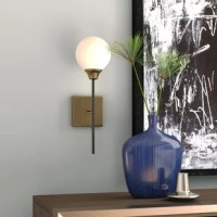 Perfect for you bath or powder room, this wall sconce is an ideal option for adding some light in your life. Featuring a single milk glass orb with brass detailing at the base, this light adds a contemporary feel to any room. Its oil rubbed bronze post attaches to a square wall fixture, which can be mounted with the bulb facing up or down depending on your needs. A dimmable feature allows you to set the perfect mood for your space when paired with a compatible switch, adding a splash of...
