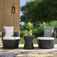 Kick back beside a buddy and enjoy your backyard with this three-piece seating group set, complete with one compact side table and two chairs. Wrapped in rattan, each weather-resistant piece is dotted with woven details for a textured and breezy look. A layer of glass serves as the tabletop, so it's easy to clean up after accidental spills. Foam-filled cushions with vinyl upholstery top both chairs to provide a bit of padding as you relax and unwind.