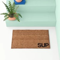"Made in the USA, this doormat is made from coarse, natural coir fibers renewably sourced from coconut husks—perfect for brushing dirt from the bottoms of boots. The word ""SUP"" is printed using vegetable dyes in the lower corner, while a vinyl non-slip backing helps keep the mat in place as you're scraping your shoes clean. Measuring 18"