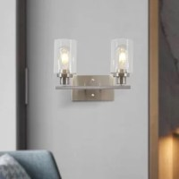 This 2-light stylish sconce features a square metal wall mount and the clear glass cylindrical shade that gently diffuses light when the fixture is illuminated, add an elegant touch to your home. The wall light fixtures design allows for this sconce to be installed in an upwards or downwards position.