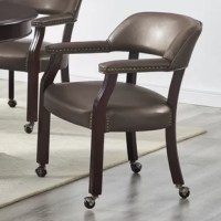 Lend a touch of traditional style to your ensemble with this parlor chair. Crafted of solid wood in a warm cherry stain, this chair features a mid backrest, fixed arms, and four carved legs on hooded caster wheels. Enveloped in easy-to-clean vinyl upholstery, this chair features antique nailhead trim for a tailored touch, while foam cushioning provides added comfort and support. This chair has a 250 lbs. weight capacity.