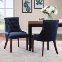With solid-hued velvet upholstery, diamond accent stitching, and button-tufted details, this tasteful dining chair is teeming with texture. Founded atop four brown-finished poplar legs, this low-profile piece is built with a solid and manufactured wood frame that supports up to 225 lbs. Its flame-retardant foam fill provides a bit of cushioning as you dine or relax, while chrome-finished nailhead trim rounds out the design with a dash of glamour. Assembly is required.