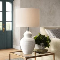 Add texture and bright lighting to your home with this trendy white ceramic table lamp. A unique curved lamp body features a white glaze with a light crackle texture, while the tan drum shade fills the room with bright illumination - perfect for placing on your wood toned accent tables for use as a reading light.