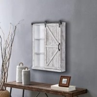 Storage solutions should not only be functional, but fashionable too. We hear from you. Reminiscent of a sliding barn door in an old farmhouse, the Winona barn door cabinet mirror offers the perfect rustic touch to any room. The fully functional door slides back and forth on rollers to reveal hidden storage space. Within the cabinet, choose to display either 3 useful shelves for treasured curios on one side or an elegant mirror on the other. Crafted of wood, the cabinet has a rustic aged white...
