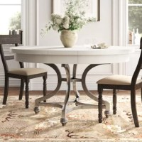 Go from cozy family meals to larger gatherings at a moment's notice with this extendable, rounded dining table. It includes a removable leaf that allows you to seat up to six people for dinner or brunch. Crafted from iron in a distressed nickel hue, its open pedestal base features petite turned feet and curved sides for elegant character. Its tabletop features a paneled design, and is finished in a neutral hue that blends in with any color palette. Plus, it's made in the USA!  Hand-curated...