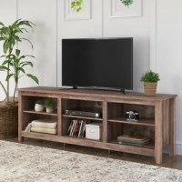 Bring some farmhouse flair to your living room look with this eye-catching TV stand as a focal point. Crafted from manufactured wood, this clean-lined piece features four tapered legs and strikes a rectangular silhouette. Its neutral finish blends easily with nearly any color palette, while natural knots and grains in the material bring a dash of rustic style. Plus, it includes six shelves for organizing your movie collection and more, while cable management cutouts help keep wires out of sight.