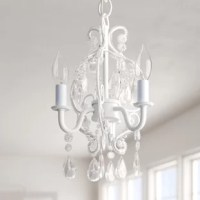 Update your baby's nursery with this charming chandelier perfect for a traditional aesthetic. Designed with a hint of glam, it showcases an airy curved wrought iron body, with a white finish, with small clear glass beading wrapped around, and large glass crystals dangling here and there. This fixture accommodates three candelabra-base incandescent lightbulbs of up to 25 W each (bulbs not included). Hardwired, this luminary is compatible with sloped ceilings.