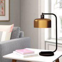 An understated, industrial design gets a contemporary refresh with this Table Lamp. Crafted from metal, this piece features a round base, a tubular body, and an arched arm in a blackened bronze or gold finish, so it's neutral enough to blend with a variety of color palettes and aesthetics. A cylindrical shade sits up top, rounding out the design with a sleek touch. A compatible 60 W medium-base bulb is not included.