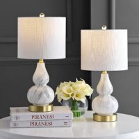 The smaller scale of this classic double-gourd table lamp makes it the perfect fashionable and functional accent for a console table or nightstand. Up top are a white linen fabric shade and brass-colored sphere finial. A classic glass lamp with a modern shape, this piece will add both light and style to a variety of rooms. This item is sold as a set of two.