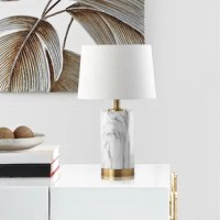 Blending the look of precious metals and high-end stone, this artful table lamp lends your space a touch of upscale appeal. Striking a clean-lined cylindrical silhouette, the body of the lamp showcases a faux-marble appearance with elegant veining, while the flush metal base and fixture sport a chic spun brass finish for a touch of midcentury modern glam. Let this light illuminate your bedside for late-night reading, or place it on a console table in the living room to brighten up a reading...