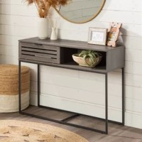 This entry table has the best of both worlds when it comes to storage. Half is an open cubby while the other half is covered by a slatted drop-down door. This long accent table has a unique powder-coated metal base that complements the boxy silhouette of the top compartment. Round out this modern slat door collection by pairing this sofa table with its matching side table, TV stand, or coffee table.