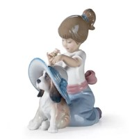 Glossy porcelain girl figurine with a red ribbon decorating her dress, putting a hat on her puppy with a flower in her hand.