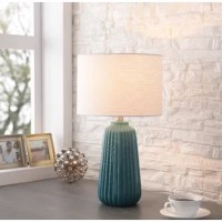A vibrant glazed ceramic base and crisp white linen fabric shade create a versatile look that complements any coastal chic living space. Deep vertical ridges create a darker color along the base of the lamp, leading to the bright light escaping from the crisp white shade. Clean lines and a modern drum shade make this piece suitable for placement on top of your contemporary end tables or nautical-inspired nightstands, while the pop of color makes this a strong accent for bohemian themed spaces.